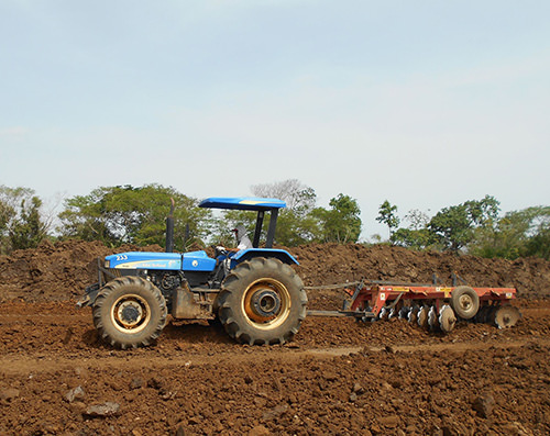 Agricultural tractor with harrow